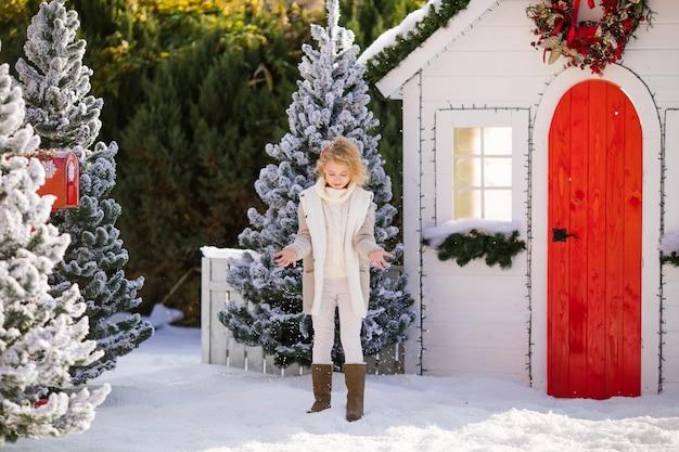 Nettes blondes mädchen, das mit schnee nahe dem kleinen haus und den schneebedeckten bäumen spielt