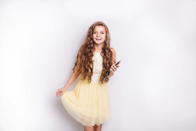 Nettes blondes mädchen, das musik auf kopfhörern auf smartphone hört, hat spaß. sie lächelt breit und spielt mit ihrem gelben kleid. sie hatte langes lockiges blondes haar