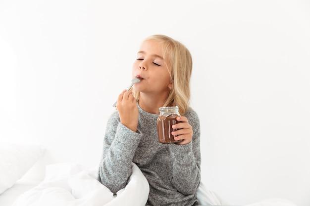 Nettes blondes mädchen, das schokoladen-haselnuss erfreut, verteilte mit geschlossenen augen, während im bett sitzend