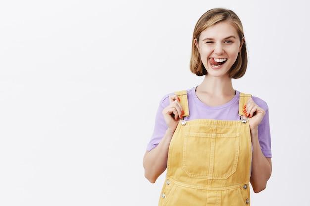 Nettes blondes mädchen, das zunge zeigt und glücklich lächelt