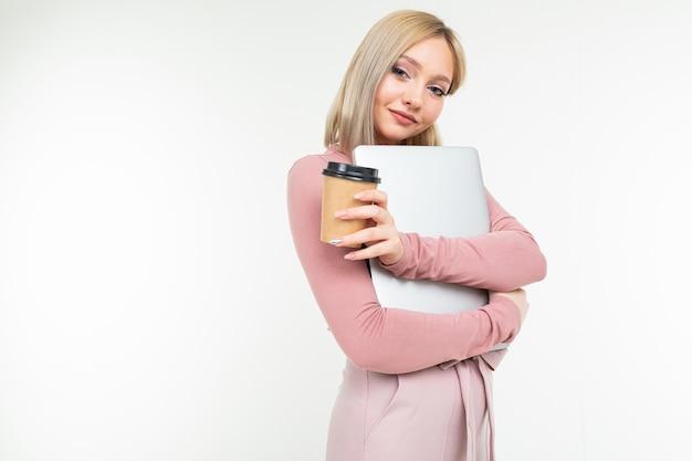 Nettes blondes mädchen in der pause mit einer tasse kaffee und einem laptop in ihren händen