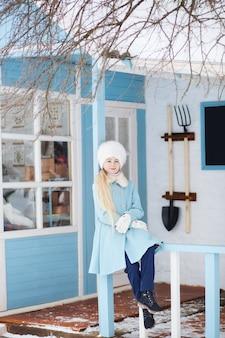 Nettes blondes mädchen in einem blauen mantel und in einem weißen pelzhut im winter. verschneites wetter. das mädchen auf der veranda des hauses. winter nach hause. model posiert auf der straße. das konzept der winterferien.