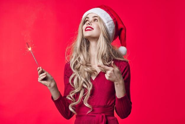 Nettes blondes mädchen in weihnachtskleidung wunderkerzen urlaub weihnachten