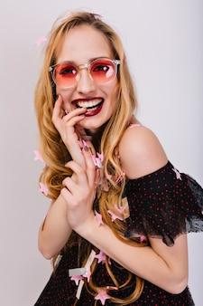 Nettes blondes mädchen mit finger im mund, glücklich und fröhlich schauend, fotoshooting auf party. hat hübsches lockiges haar, schönes lächeln. trägt ein stilvolles schwarzes kleid und eine rosa brille. isoliert..
