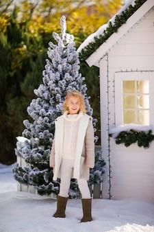 Nettes blondes mädchen nahe dem kleinen haus und den schneebedeckten bäumen. neujahr und weihnachten
