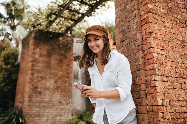 Nettes braunäugiges mädchen mit lächeln wirft neben backsteingebäude auf. frau in der kappe und im weißen hemd, die smartphone halten.