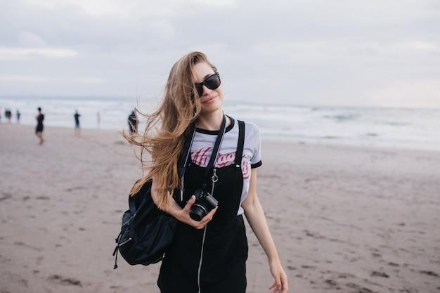 Nettes braunhaariges mädchen mit kamera, die auf natur in bewölktem tag aufwirft. außenaufnahme der gutaussehenden dame mit dem schwarzen rucksack, der um strand geht.