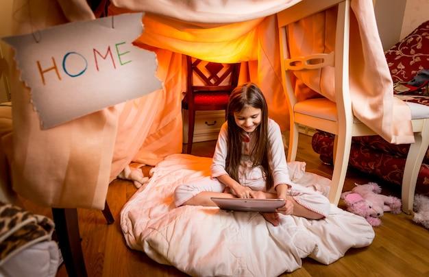 Nettes brünettes mädchen, das im schlafzimmer auf dem boden sitzt und digitales tablet benutzt