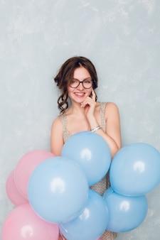 Nettes brünettes mädchen, das in einem studio steht, breit lächelt und blaue und rosa luftballons hält. . sie berührt ihre brille