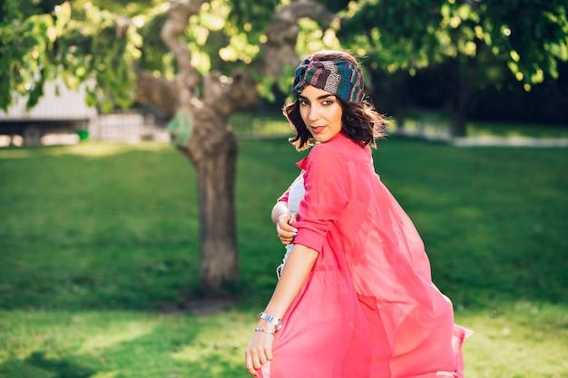 Nettes brünettes mädchen im bandana, das im sommerpark geht. sie trägt weiße kleidung, ihr langes rosa hemd fliegt im wind. blick von hinten.