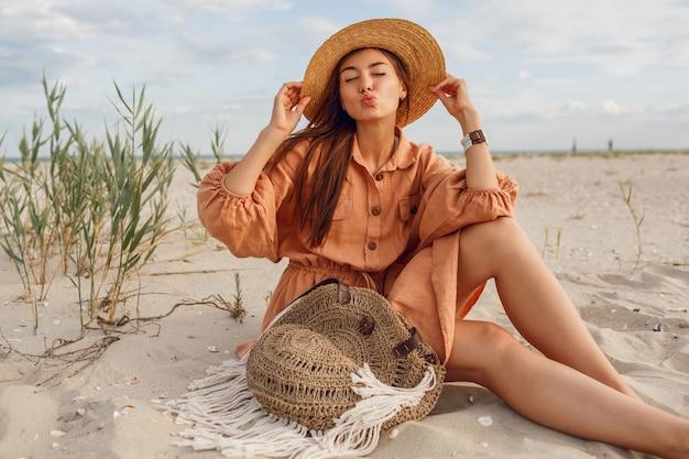 Nettes brünettes mädchen senden kuss und entspannung am strand. tragen von sommerlichen modischen leinenkleidern. strohhut und boho-tasche.