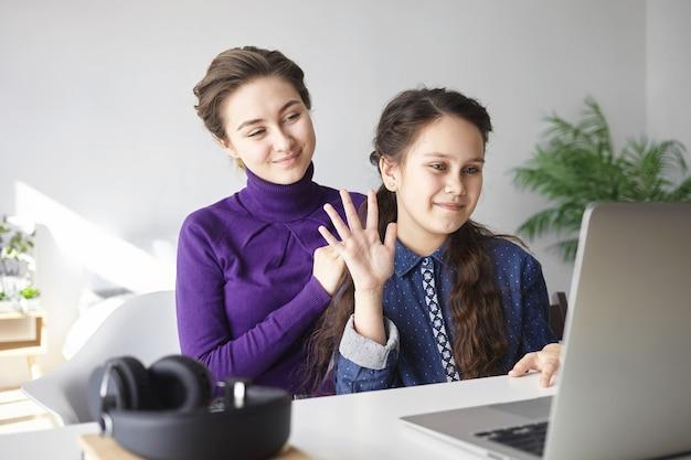 Nettes brünettes weibliches kind, das hand am laptop-bildschirm unter verwendung des video-chats zusammen mit ihrer jungen mutter im schlafzimmer winkt