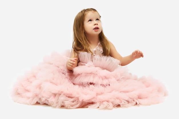 Nettes charmantes kleines mädchen mit losen glatten haaren, die auf boden mit ballettrock sitzen, der ihre beine und füße bedeckt