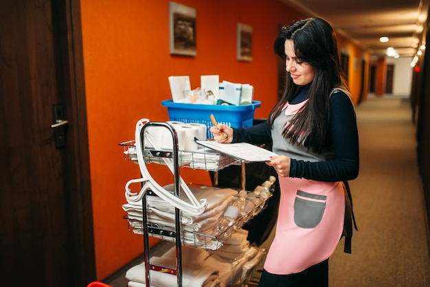 Nettes dienstmädchen in uniform macht sich notizen nach der reinigung des zimmers, wagen mit reinigungsmitteln, hotelkorridor interieur. professionelle hauswirtschaft, putzfrau job
