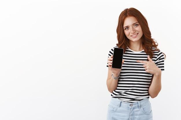 Nettes dummes rothaariges mädchen in gestreiftem t-shirt, das smartphone hält, das auf das mobile display zeigt, den kopf neigt und sorglos lächelt, ihre internet-profilseite zeigt, weiße wand steht, app empfehlen