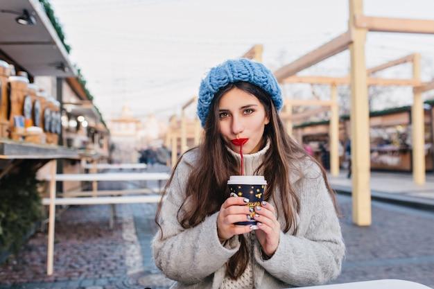 Nettes dunkelhaariges mädchen mit funkelnder maniküre, die tee auf der straße während des winter-fotoshootings trinkt. schüchterne junge dame der schüchternen im trendigen blauen hut, der mit tasse kaffee am kalten morgen aufwirft.