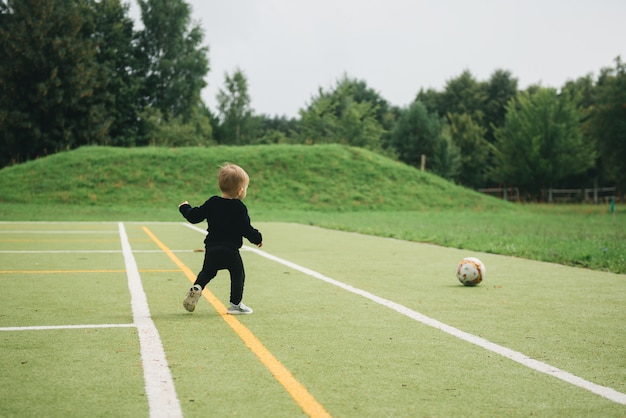 Nettes einjähriges kind, das fußball mit einem ball auf kunstrasen spielt