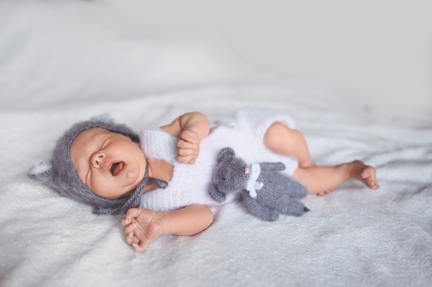 Nettes emotionales neugeborenes kind, das baby gähnt, das im kinderbett in einem strickanzug mit spielzeug schläft.