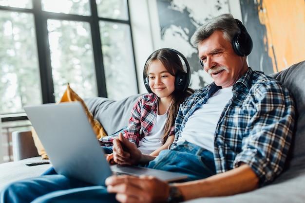 Nettes enkelkind und ihr großvater hören musik auf digitalem tablet, während sie auf dem sofa sitzen.