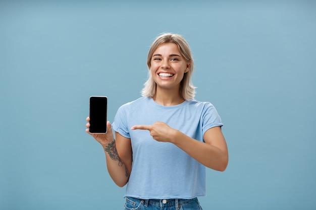 Nettes enrgisiertes mädchen, das smartphone zeigt. charmante blonde junge frau mit kühlen tätowierungen, die vor glück und freude lachen und lächeln und auf gerät zeigen telefon zeigen