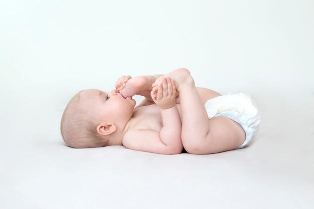 Nettes entzückendes baby, das auf dem bett liegt