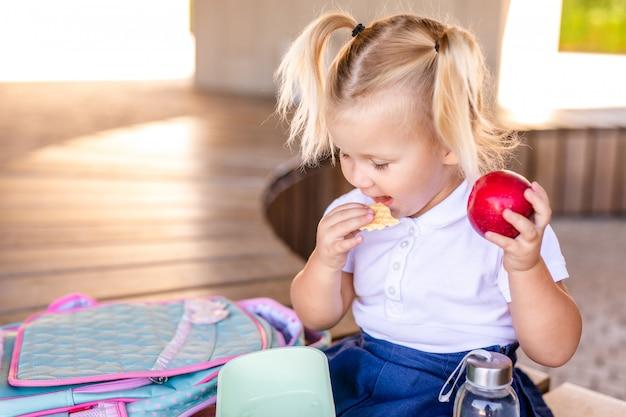 Nettes entzückendes kaukasisches kleinkindbaby, das sitzt und isst