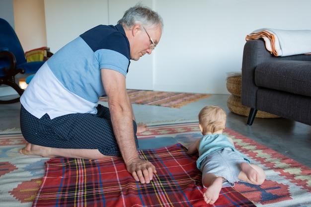 Nettes entzückendes kind, das auf bauch liegt und zu hause auf weichem boden spielt. ernsthafter großvater, der auf teppich nahe enkelkind sitzt und kleines kind beobachtet. kindergarten-, familien- und kindheitskonzept
