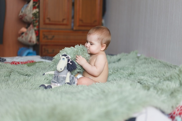Nettes entzückendes neugeborenes baby von 3 motten mit windeln. glückliches kleines kleines mädchen oder junge, die die kamera betrachten. trockener und gesunder körper und haut für kinderkonzept. kinderzimmer