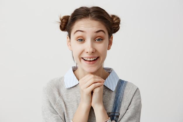 Nettes erwachsenes mädchen mit odango-frisur mit lächeln, das fäuste zusammenhält. aufgeregte schöne frau, die mit glück glänzt, nachdem sie heiratsantrag erhalten hat. gesichtsausdrücke