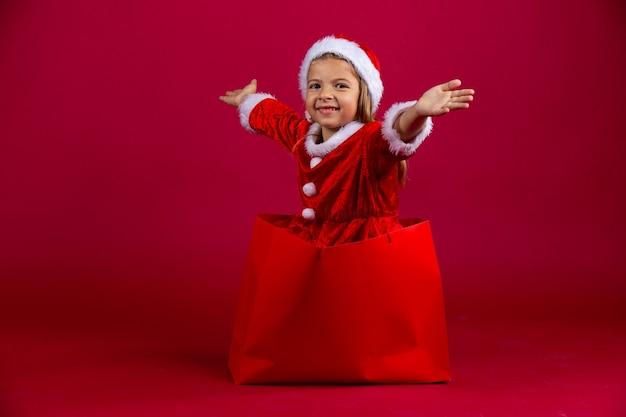 Nettes, fantastisches, sehr glückliches kaukasisches kleines mädchen entkommen aus der roten geschenkpackung. neujahr. isolierte rote wand. .