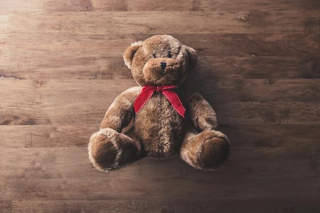 Nettes flaumiges lächelndes braunes teddybärspielzeug auf hölzernem hintergrund