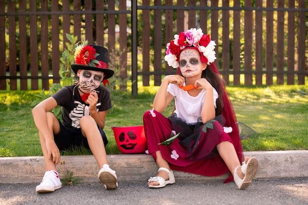 Nettes freundliches mädchen und junge in halloween-kostümen, die an der straße vor der kamera gegen holztor sitzen und süßigkeiten am sonnigen tag haben
