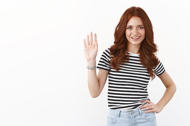 Nettes, freundliches und lässiges junges rothaariges kaukasisches mädchen in gestreiftem t-shirt, winkt mit erhobener hand in grußgeste, lächelt freudig, willkommen freund, lädt gast ein, sagt hallo oder hallo, weiße wand