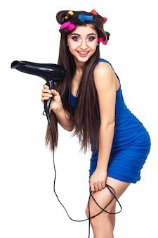 Nettes fröhliches junges mädchen im blauen kleid mit lockenwicklern im haar und mit haartrockner in der hand. isoliert auf weißer oberfläche