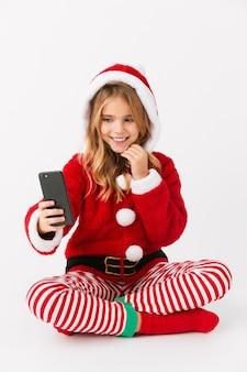 Nettes fröhliches kleines mädchen, das weihnachtskostüm isoliert trägt, handy hält, ein selfie nehmend