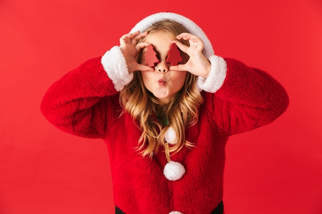 Nettes fröhliches kleines mädchen, das weihnachtskostüm isoliert trägt