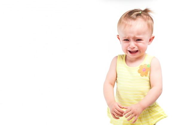 Nettes fröhliches kleines mädchen im gelben kleid, weinend