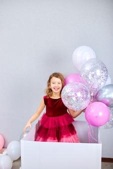 Nettes, fröhliches kleines mädchen im rosa kleid schaut aus der großen geschenkbox mit luftballons