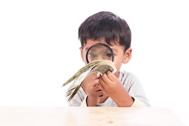 Nettes gebrauchvergrößerungsglas des kleinen jungen, das geld schaut