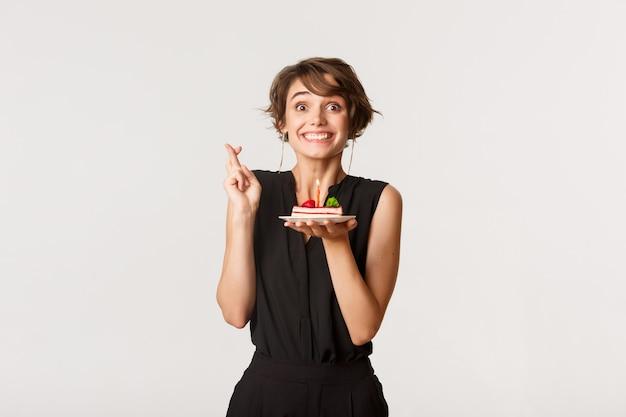 Nettes geburtstagskind kreuzt die finger viel glück und wünscht sich auf geburtstagstorte