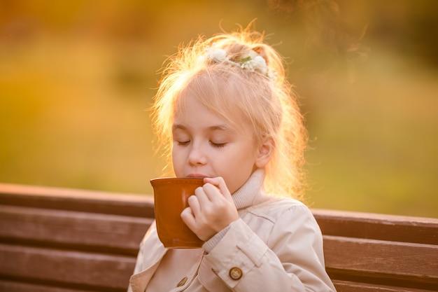 Nettes gelocktes kind im hellen mantel mit einer großen schale heißem kakao im herbstpark