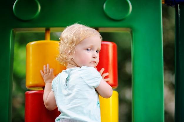Nettes gelocktes kleinkindmädchen, das spaß auf spielplatz im freien hat
