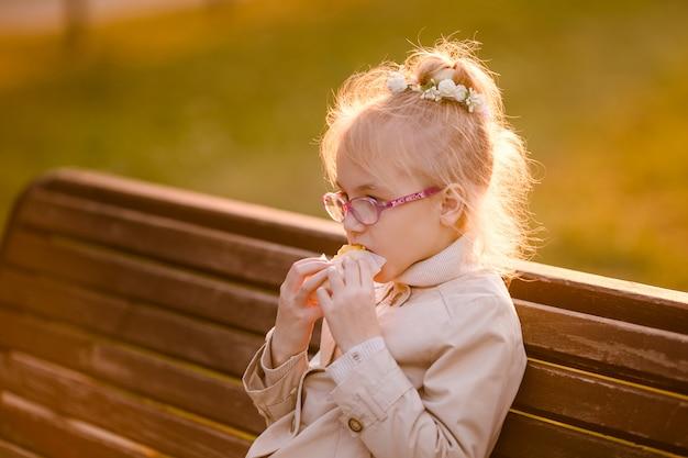 Nettes gelocktes lächelndes kind im hellen mantel mit einer großen schale heißem kakao im herbstpark