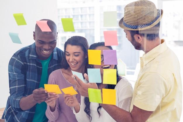 Nettes geschäftsteam, das klebende anmerkungen gegen glas im kreativen büro hält