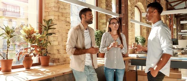 Nettes gespräch. drei junge kollegen in freizeitkleidung halten kaffeetassen und diskutieren etwas, während sie im modernen büro stehen. kaffeepause.