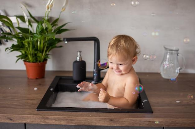 Nettes glückliches baby mit dem spielen mit wasser und schaum in einer küchenspüle zu hause