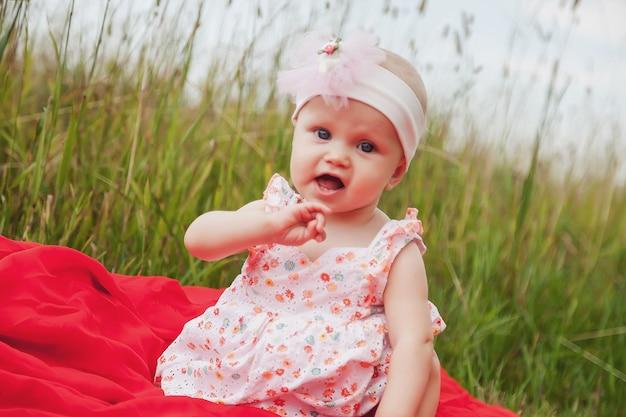 Nettes glückliches blondes mädchen mit blauen augen 8 monate alt im gras. konzeptionelles foto für bildung, gesunde kindheit, elternschaft, designlandschaft. perfekter kaukasischer säugling auf natursommer. platz für website kopieren