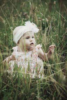 Nettes glückliches blondes mädchen mit blauen augen 8 monate alt im gras