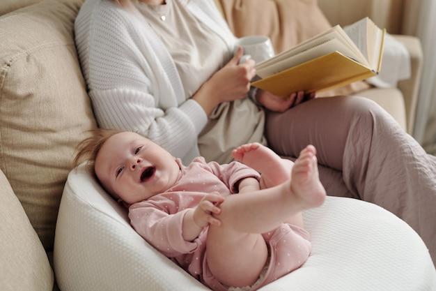 Nettes glückliches kind, das von ihrer mutter im kleinen bett liegt