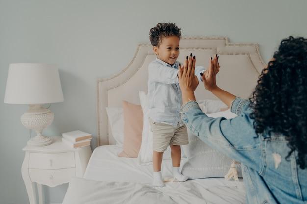 Nettes glückliches kleines afroamerikanisches kind, das mit seiner mutter im schlafzimmer zu hause spielt